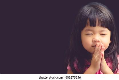 Little girl praying in the morning.Little asian girl hand praying,Hands folded in prayer concept for faith,spirituality and religion.Black