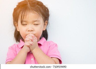 Little girl praying in the morning.Little asian girl hand praying,Hands folded in prayer concept for faith,spirituality and religion.Pray for Florida concept.Vintage tone.