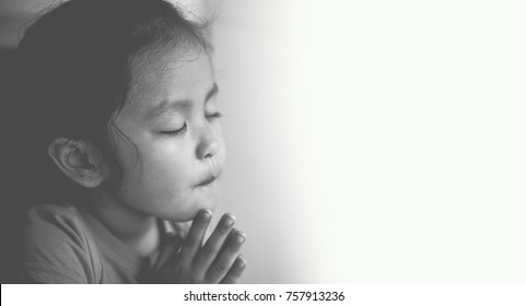 Little girl praying in the morning.Little asian girl hand praying,Hands folded in prayer concept for faith,spirituality and religion.Black and white.