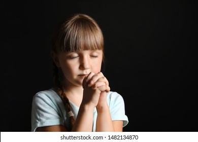Little girl praying on dark background