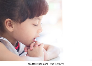 Little girl praying on the white table in the morning.Little asian girl hand praying,Hands folded in prayer concept for faith, spirituality and religion.