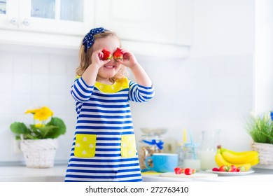 Little girl preparing breakfast in kitchen. Healthy food for children. Child drinking milk and eating fruit. Happy preschooler kid enjoying morning meal, cereal, banana and strawberry. Kids eating.