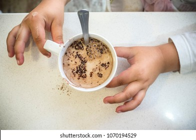 Little girl preparing her afternoon snack. A cup of chocolate powder with milk