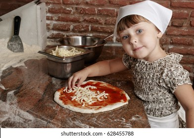 Little girl preparing pizza on the professional kitchen (old italian pizzeria). Adding cheese to pizza