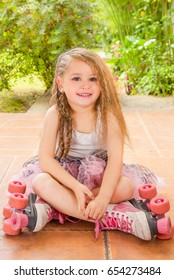Little girl preschool sitting on ground wearing her roller skates and crossing her legs, in a garden background