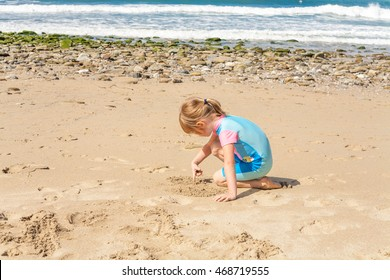 Little girl of preschooler age drawing in the sand on a Cornish beach with ocean scene background. Cute kid on summer vacation. Cornwall tourism