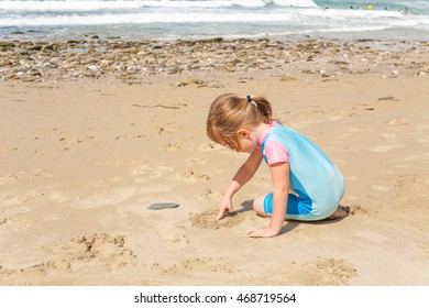 Little girl of preschooler age drawing in the sand at the beach with ocean scene background. Close up of cute kid on vacation.