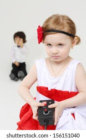 Little girl presses button on control console and boy sits behind she on grey background. Focus on girl.