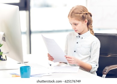 Little girl pretending to be businesswoman and working with documents and computer in office