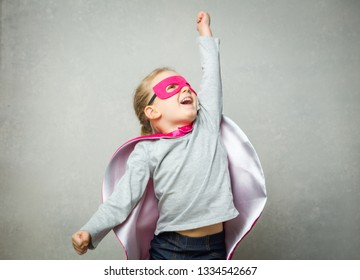 Little girl pretending that she is flying wearing a cloak and mask