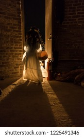 Little girl in princes dress on a halloween entering a door with light