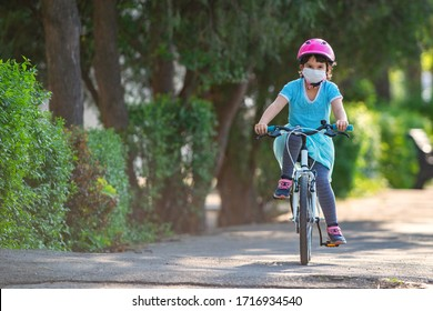 Little girl in protective medical mask rides a bicycle.