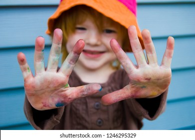 Little girl proudly holds up messy, colorful hands, covered in paint. Blue aluminum siding in background.