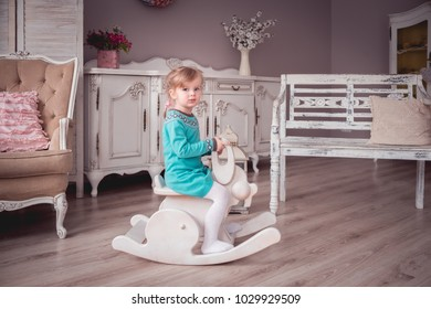 Little girl in a provence interior riding a rocking bunny