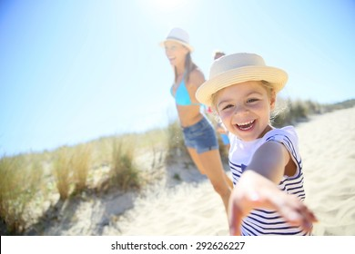 Little girl pulling parents' arms to run to the beach