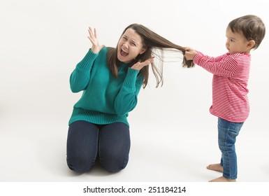 A little girl pulls her older sister hair