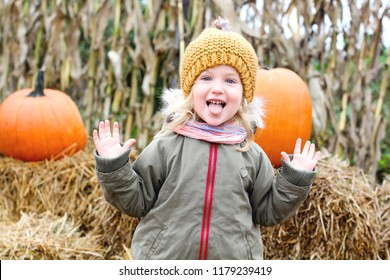 Little girl with pumpkin outdoor having fun in autumn park.
