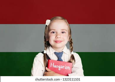 Little girl pupil with book against the Hungary flag background. Learn hungarian language, Hungary concept