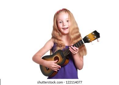 little girl in purple dress playing the ukulele