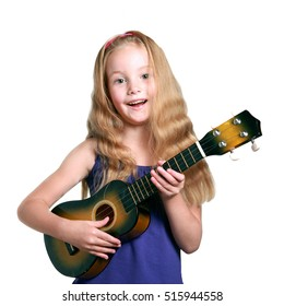 little girl in purple dress playing the ukulele against white studio background