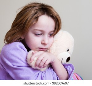 Little girl in purple pajamas holding and protecting herself with teddy bear.