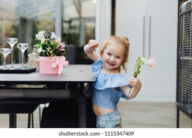 Little girl puts flowers on table, indoor