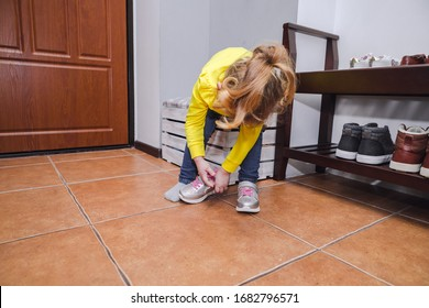 The little girl puts on her shoes.
