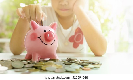 Little girl putting coin into piggy bank for saving with pile of coins on table at home.A pink piggy bank are smile and happy while standing over pile of coins.