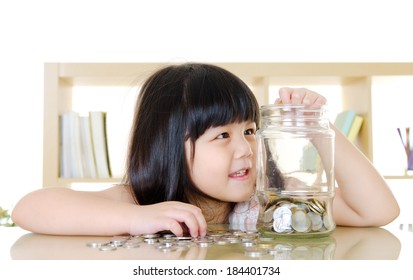 Little girl putting coins into the glass bottle. money saving concept.