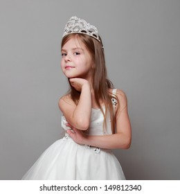 Little girl is putting on a diamond diadem on Beauty and Fashion/Young princess smiling and posing for the camera