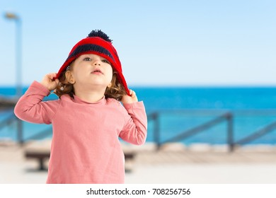 Little girl puttining on a Christmas hat