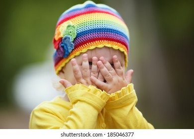 little girl with rainbow hat is playing hide-and-seek