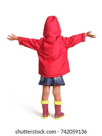 Little girl in raincoat and rubber boots, isolated on white background