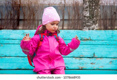 little girl in a raincoat sits on a bench