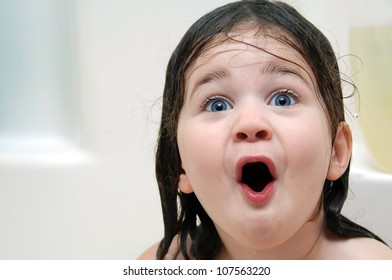 Little girl reacts to bathtime.  Her mouth is open in amazement and her hair is soaking wet.