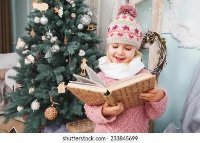 Little girl read the book around the Christmas tree