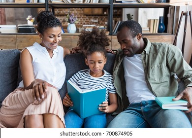 Little girl reading a book with her parents sitting on a couch beside her
