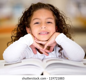 Little girl reading a book at the library