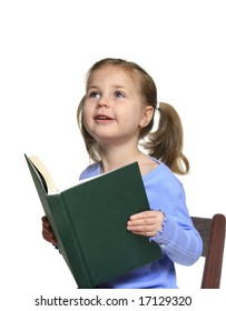 Little girl reading a book looking excitedly up at her teacher or parent
