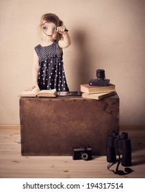 little girl reading book with magnifier