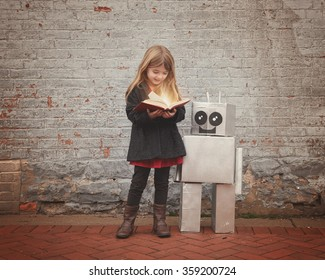 A little girl is reading a book with a metal cardboard robot next to her against a brick wall for an education or creativity concept