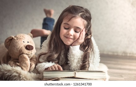 little girl reading a book with a Teddy bear on the floor in a cozy living room at home, beautiful emotions, the concept of relaxation and friendship