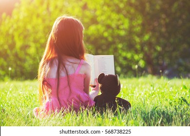 Little girl reading book with teddy bear toy. Friendship concept