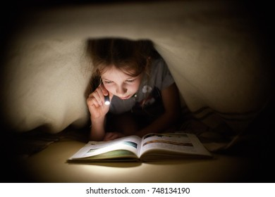little girl is reading a book under a blanket with a flashlight in a dark room at night