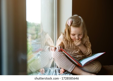 Little girl is reading a book while sitting near window