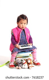 little girl reading a book while sitting on a stack of books