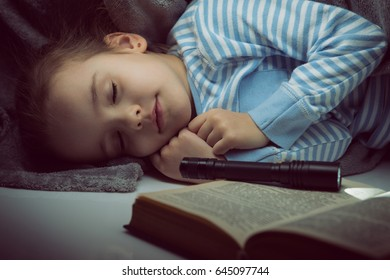 Little girl reading fairy tales book under the covers at the evening with lantern and sleeps after reading. Cute kid playing before going to sleep, image toned.