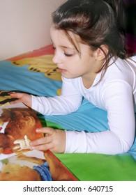 Little girl reading a kids book