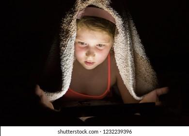 Little girl reading at night under blanket