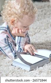 Little girl reading on the floor